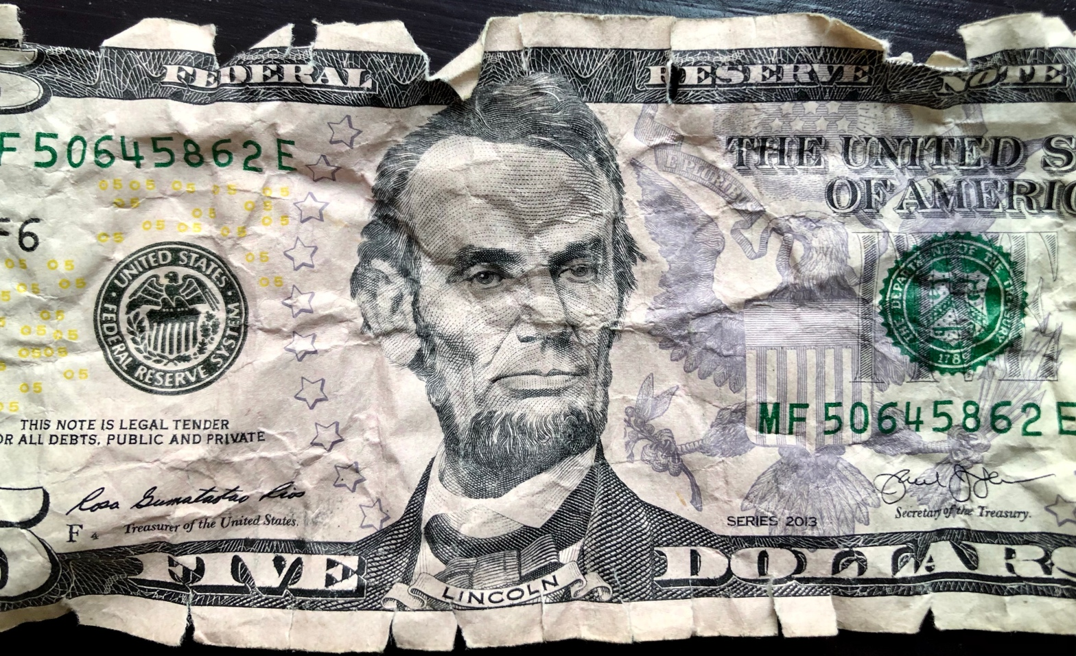 Ragged five dollar bill